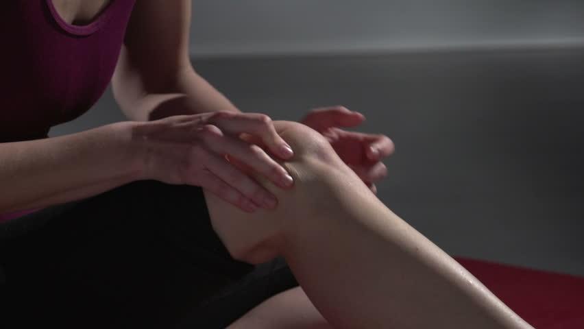 Knee pain, woman rubbing her knee