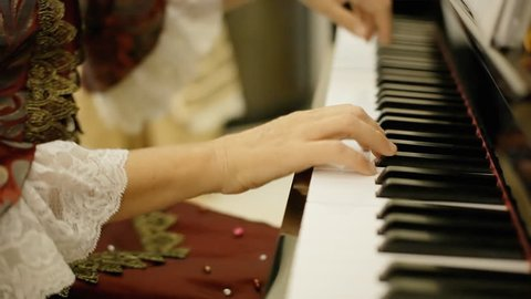 A female pianist, wearing clothes of the 18th century nobility, playing a rondo by Wolfgang Amadeus Mozart on a piano.
