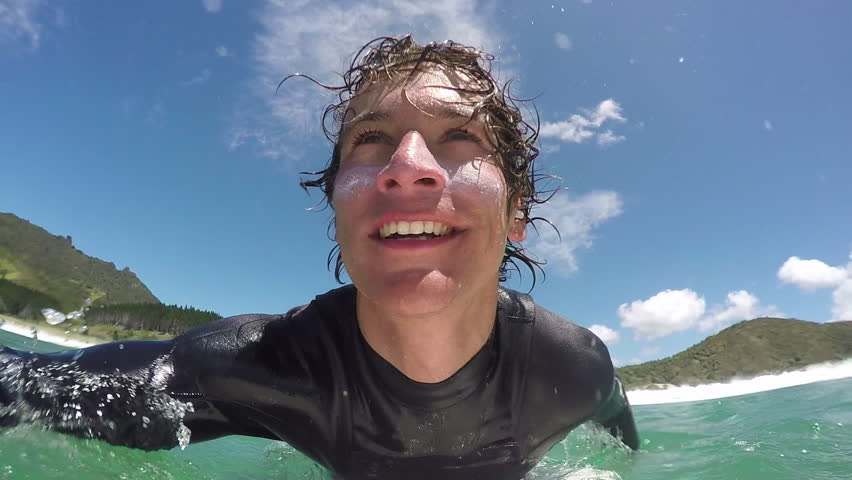 SLOW MOTION CLOSE UP: Happy young surfer duck diving under the waves and paddling out towards the lineup. Cheerful surfer dude surfing in New Zealand ocean