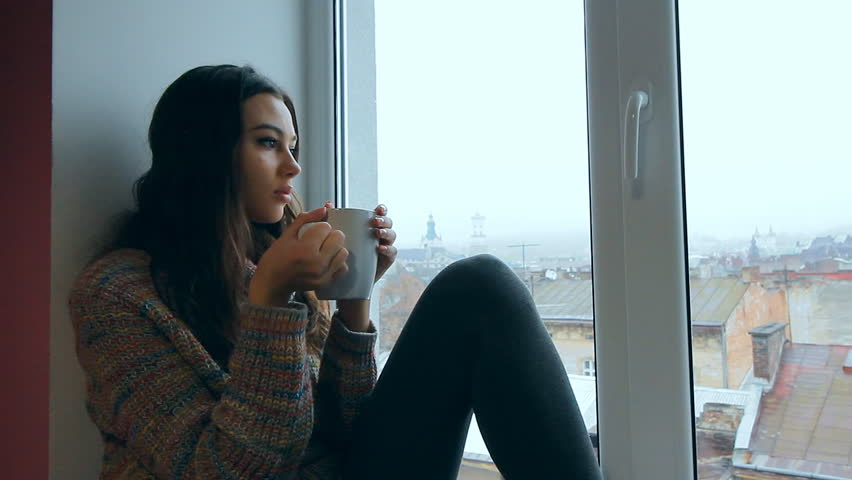 Close up view of a young beautiful girl sitting on a windowsill at the window overlooking an old european city and drinking hot coffee or tea from a mug. Portrait of the cute girl wearing sweater | Shutterstock HD Video #22175965