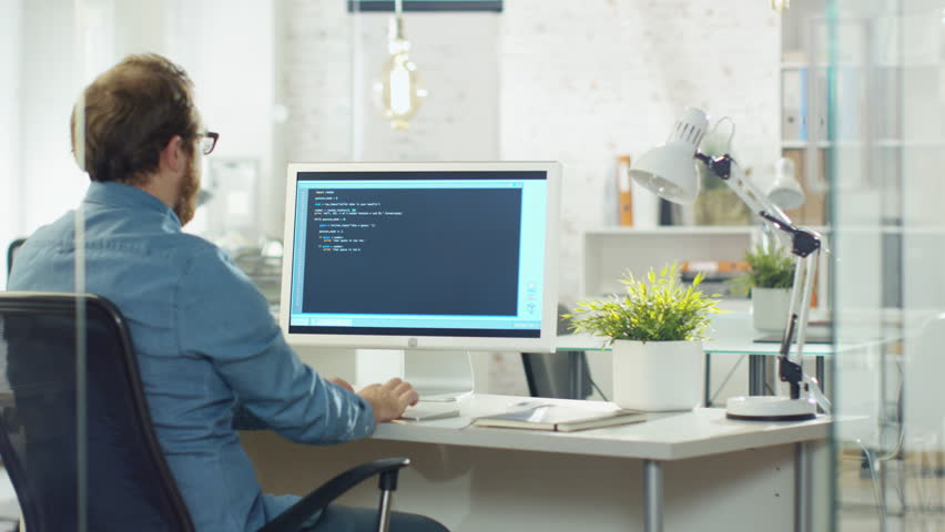 Young Bearded Developer Writes Code on His Desktop Computer. He Works in a Modern Office. Shot on RED Cinema Camera in 4K (UHD). | Shutterstock HD Video #22195345