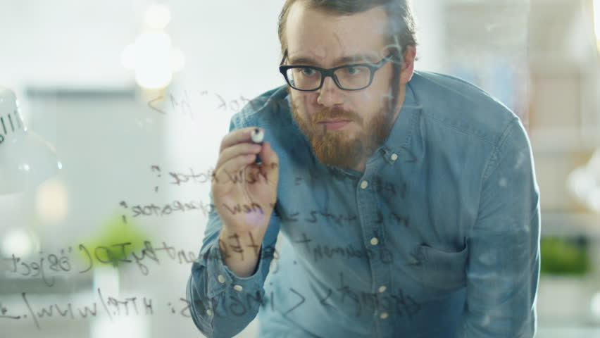 Close-up of a Man Writing Formulas on a Glass Whiteboard. Shot on RED Cinema Camera in 4K (UHD).