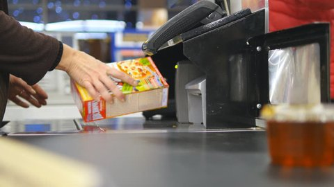 Shopper paying for products at checkout. Foods on conveyor belt at the supermarket. Cash desk with cashier and terminal in hypermarket. Working of cashier. Shopping at store. Close up