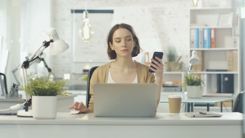 Portrait Shot of a Creative Woman Sitting at Her Desk. She Holds Smartphone and Consults Her Notebook. She Sits in a Light and Modern Office. Shot on RED Cinema Camera in 4K (UHD).