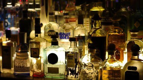 HAMBURG, GERMANY, DECEMBER 2016: Assorted spirit drink bottles behind the bar under low light. Vodka, gin, tequila, Pernod and other drinks are visible. Racking focus, focus pulling.