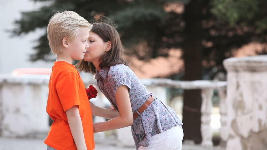 Little boy giving his girlfriend a bouquet girl kissing him in little boy giving his girlfriend a bouquet girl kissing him in turn and taking his hand stock footage video 2227315 shutterstock altavistaventures Images