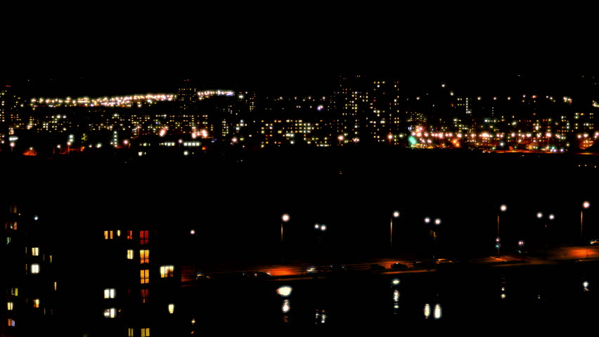 Night Life. City lights twinkle, windows of high-rise buildings light up and go out, cars with headlights drive on roads. (av31623c)