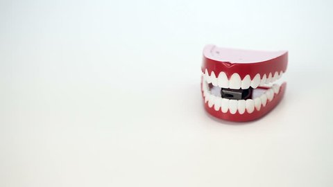 This is a video of toy chattering teeth moving on a white background to symbolize fun concepts of comedy,dentistry,etc.