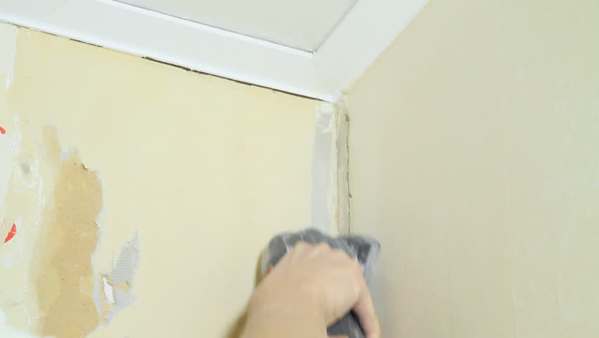 Using a sander on a wall, preparing for wallpaper.