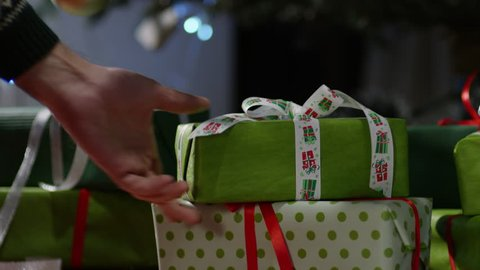 4K  Hand puts wrapped gift box under the christmas tree.  Shot on RED EPIC Cinema Camera.
