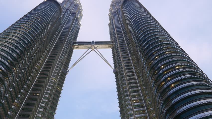 KUALA LUMPUR, MALAYSIA - FEBRUARY 27, 2015: Smooth pan dolly shot Petronas Twin Towers Skybridge in dusk, up view vertical angle shot. Camera sliding left, showing impressive skyscraper construction