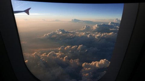 Looking out aircraft window to beautiful sunset and cumulus cloudscape. Then camera moving back to plane saloon. Flying on cruising height, beautiful clouds backlit by evening sun