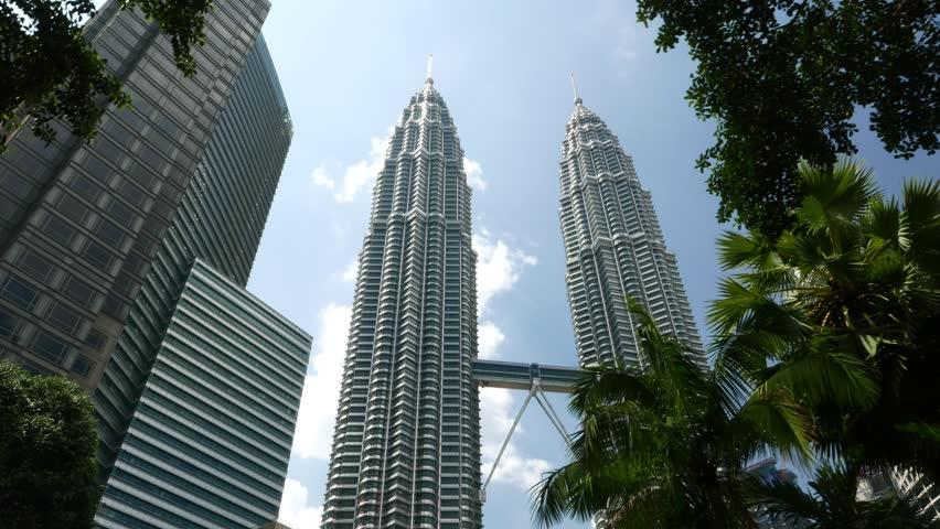 KUALA LUMPUR, MALAYSIA - FEBRUARY 27, 2015: KLCC Petronas Twin Towers from behind the trees, high angle view, Kuala Lumpur City Centre Park area. Sunny day and blue sky.