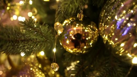 A christmas tree decorated with sparkly gold bowknot, christmas tree toys and shining lights surrounded by glitter floor. Christmas tree gold bokeh effect on background.