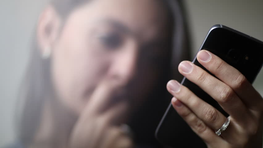 Woman with a concerned looking face on her mobile cellphone.  | Shutterstock HD Video #22390660