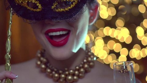 Beautiful sexy woman wearing venetian masquerade mask at party drinking champagne over holiday glowing background. Holiday make up, red lips, closeup. Full HD 1920x1080p slow motion video