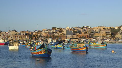 MALTA, MARSAXLOKK - DECEMBER 2013: Multi-Coloured Fishing Boats & Town; Marsaxlokk Malta