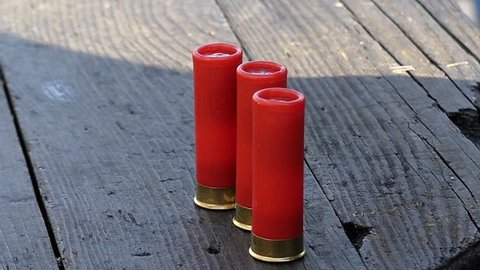 Three Red Cartridges on a Table. Cartridges For a Pump-Action Gun.