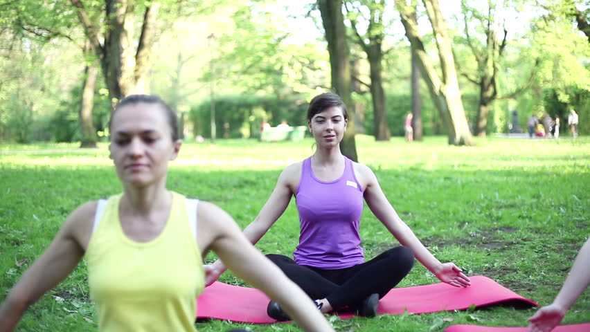 Beautiful young women meditating in the park, dolly shot