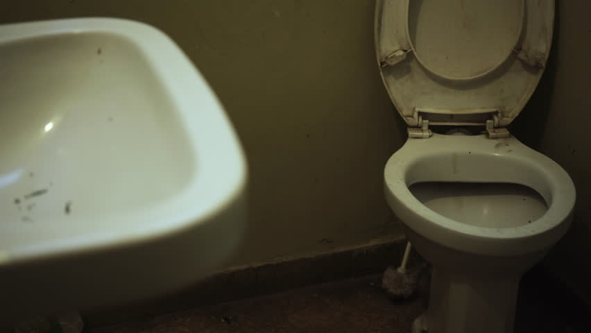 tracking shot of a dark filthy public bathroomtoilet and sink