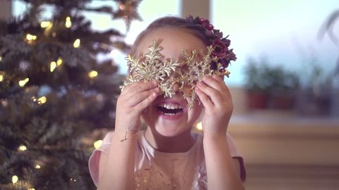 Happy Christmas little girl having fun at home, near Decorated Christmas tree. Laughing child celebrating Xmas and New Year Winter Holidays, Playing with baubles. Slow motion 240 fps. Full HD 1080p