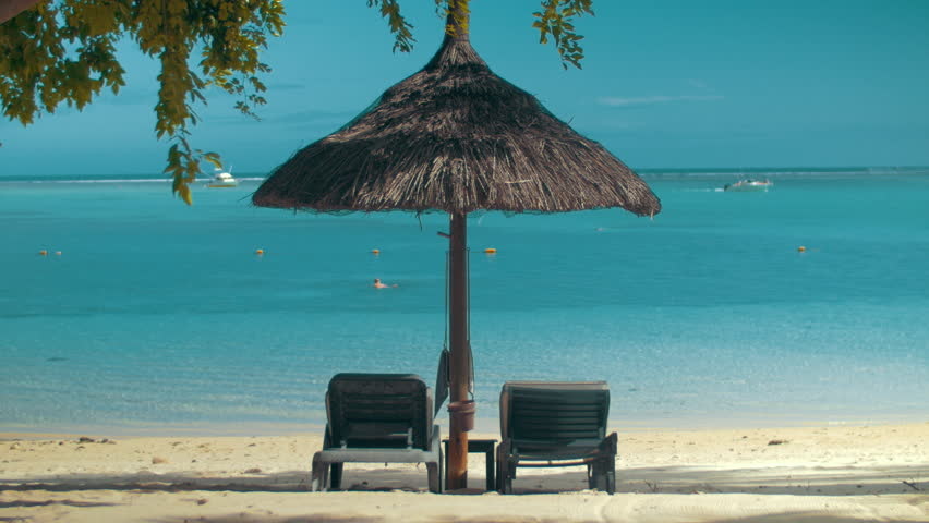Summer vacation scene. Empty chaise longues under straw sun umbrella on the ocean coast. Beach with white sand and pure blue water. Swimming woman and yachts in the distance. Holidays in Mauritius