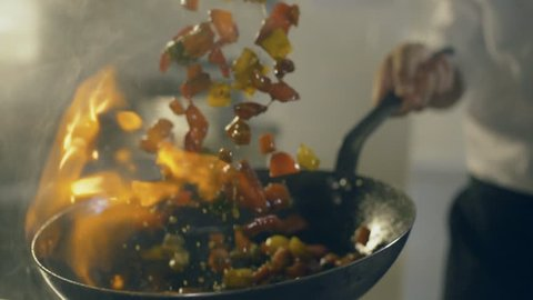 Chef in restaurant kitchen doing flambe on vegetables, close up