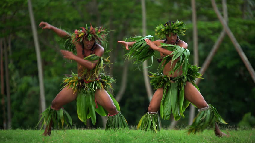 Young Tahitian males performing war dance style hula dance outdoors barefoot in traditional costume Tahiti French Polynesia South Pacific