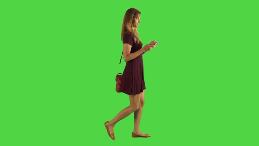 Young woman walking sideways and texting angrily in a full body shot over a green screen. Two takes. | Shutterstock HD Video #22489975
