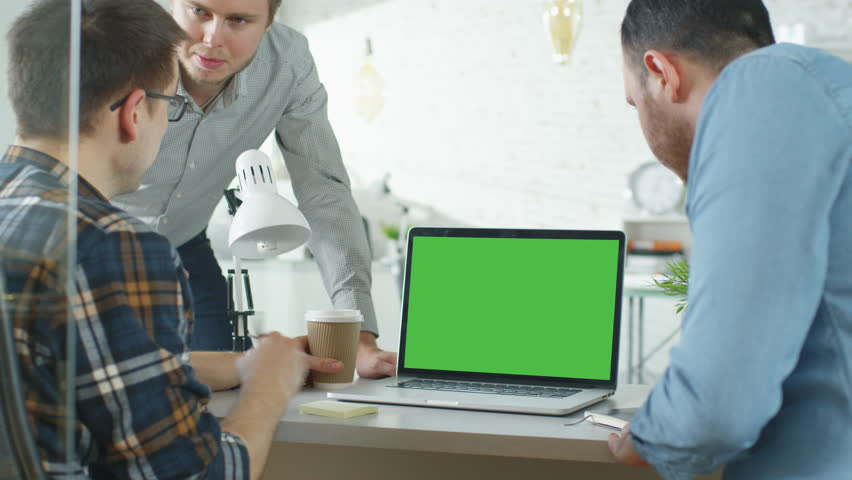 Three Creative Men Discuss Business around Green Screened Laptop. They're in Bright Modern Office.Shot on RED EPIC (uhd).