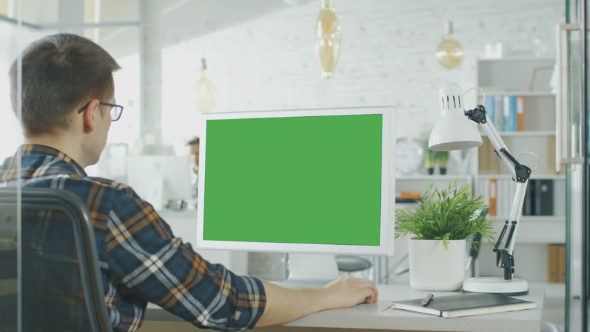 Close-up of a Man Sitting at His Desk with Green Screen PC on the Table. In Background Blurred and Brightly Lit Office where People go Through Office Routine. Shot on RED EPIC (uhd).