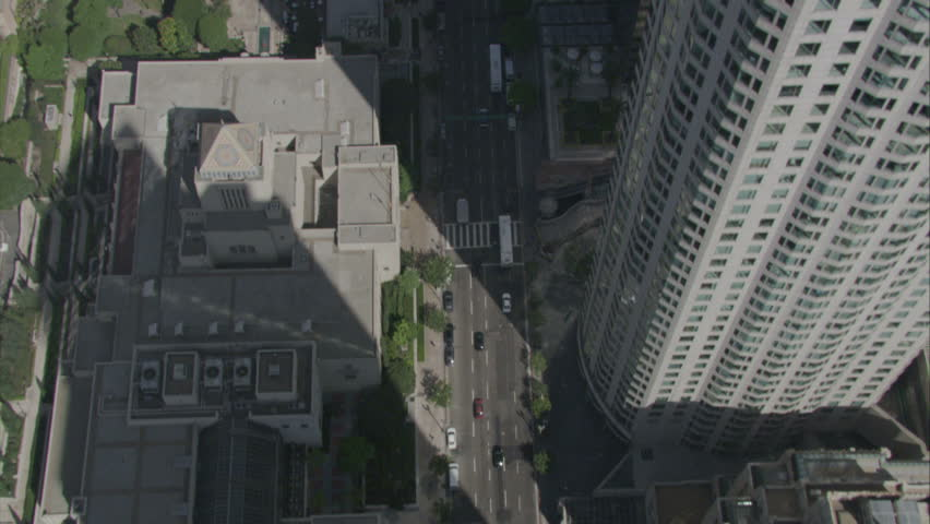 aerial fly by over busy downtown area, buildings casting shadows over the streets circa 2009