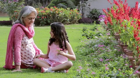 WS Grandma sits with granddaughter (6-7) in backyard playing with flowers / India