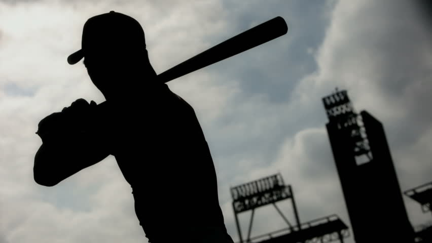 Silhouetted baseball player taking practice swings