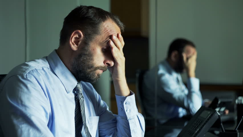 Sad, tired businessman sitting by desk in office