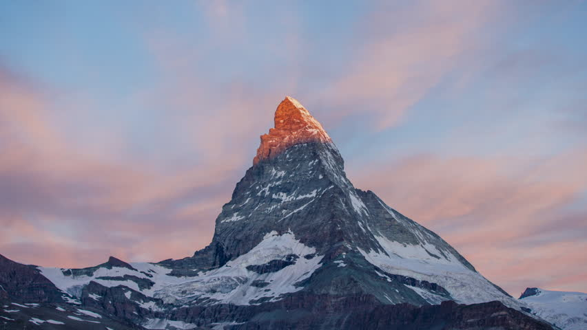 Dawn, sunrise time lapse of the amazing matterhorn mountain in the Swiss Alps. the sky lights up in an incredible display of colour followed by the shadow lowering over the mountain | Shutterstock HD Video #22567078