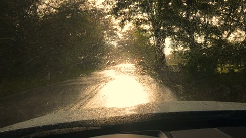 Inside of a car, driver place point of view. Driving country road at rainy weather day. Water drops on wet windshield glass. Cleaning with wipers. Sunshower sun light at sunset.