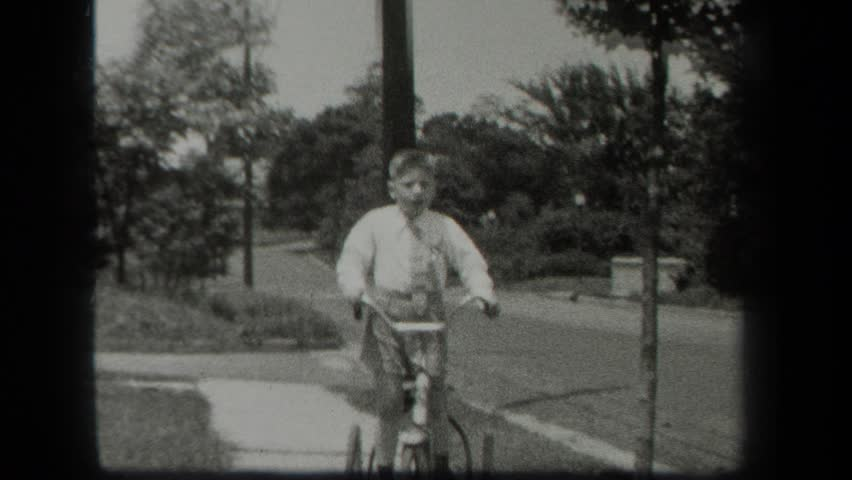 NEW YORK 1939: a boy and his bicycle on the sidewalk at daytime | Shutterstock HD Video #22597885