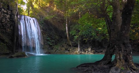 Clear waterfall flowing down turquoise clean river surrounded by jungle trees. Perfect place for relaxation in wild nature. Rainforest full of green plants. Summer time in remote forest