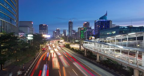 Day to night time lapse with a zoom in effect of heavy traffic rushing along the crowded Jalan Sudirman, the main avenue in Jakarta business district in Indonesia capital city.