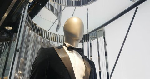 Elegant male mannequin presenting luxury suits tuxedo and male fashion accesories rotating on the window-shopping of Champs Elysees in Paris, France
