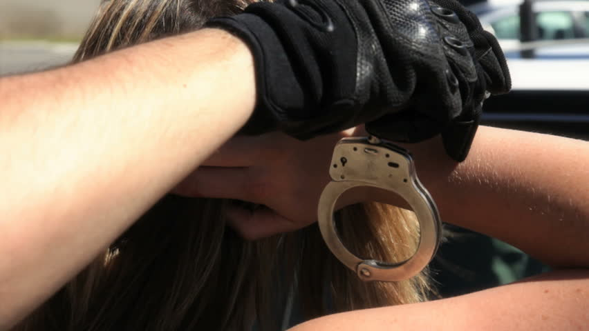 Female getting handcuffed by a police officer