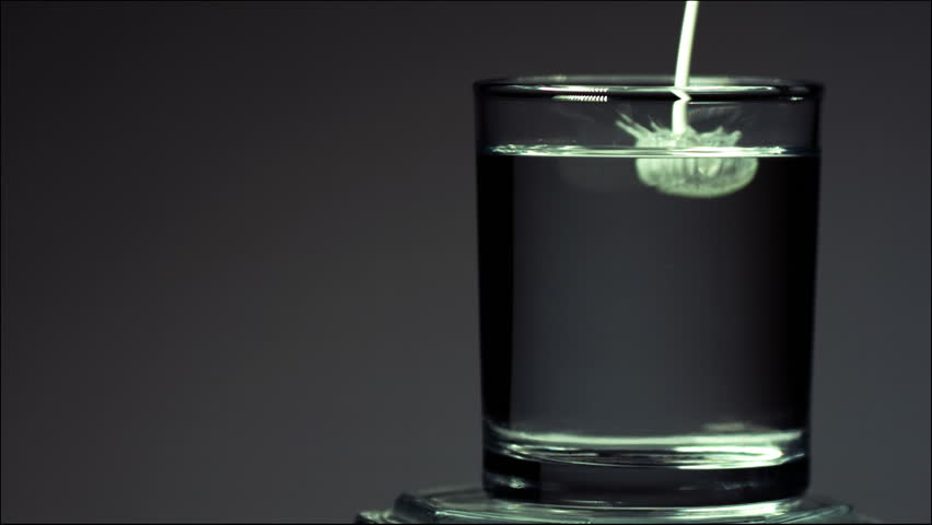 Milk is poured into a glass of water in slow motion