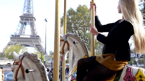 Young blonde woman portrait smiling and having fun on carousel in front of the Eiffel Tower in Paris, France.