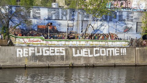 GERMANY - CIRCA MAY 2016 - Refugees Welcome graffiti on wall, close up, Berlin, Germany