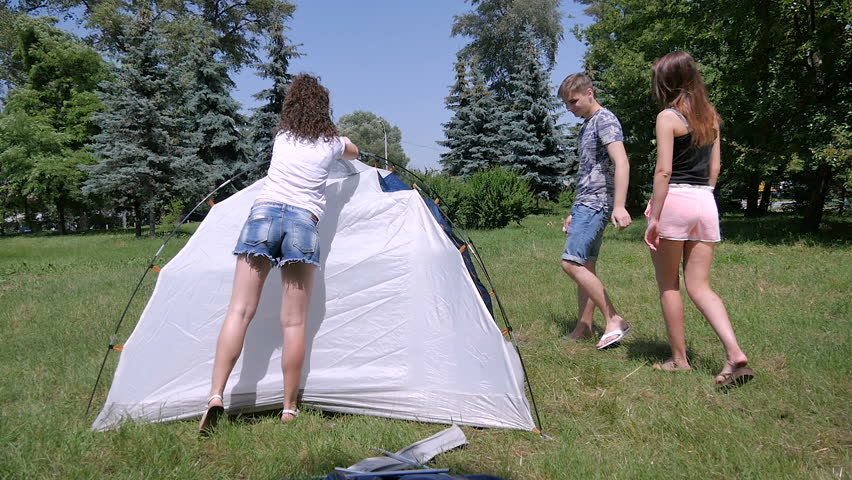 Three people have a good time near tent in park - HD stock video clip & Cute Curly Girl And Young Guy Pitches Tent In Park Stock Footage ...