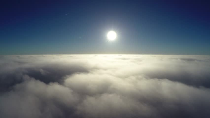 Aerial bird-eye view flying low above thick clouds towards bright sun beautiful contrast showing the crisp blue sky the darker atmosphere above bright sunshine and slowly moving clouds below 4k