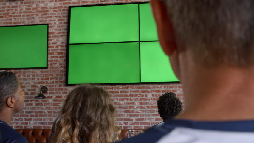 Friends Watching Game In Sports Bar Shot In Slow Motion