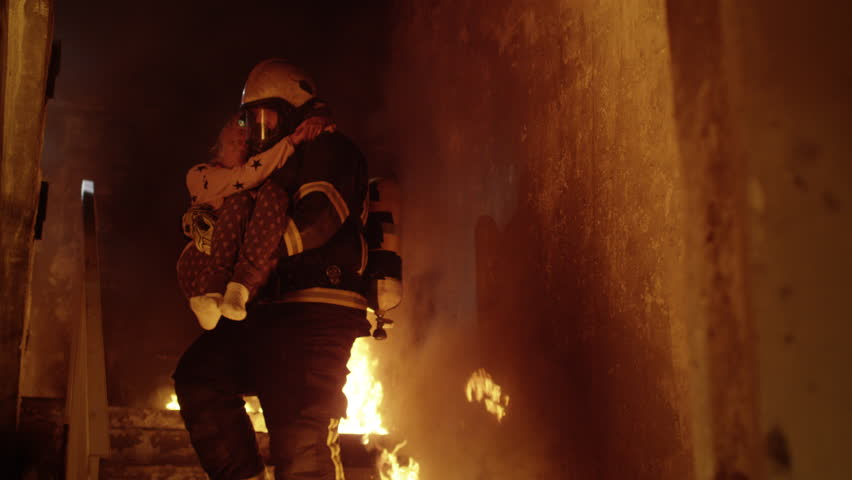 Burning Building. Group Of Firemen Descend on Burning Stairs. One Fireman Holds Saved Girl in His Arms. Shot on RED Cinema Camera in 4K (UHD).