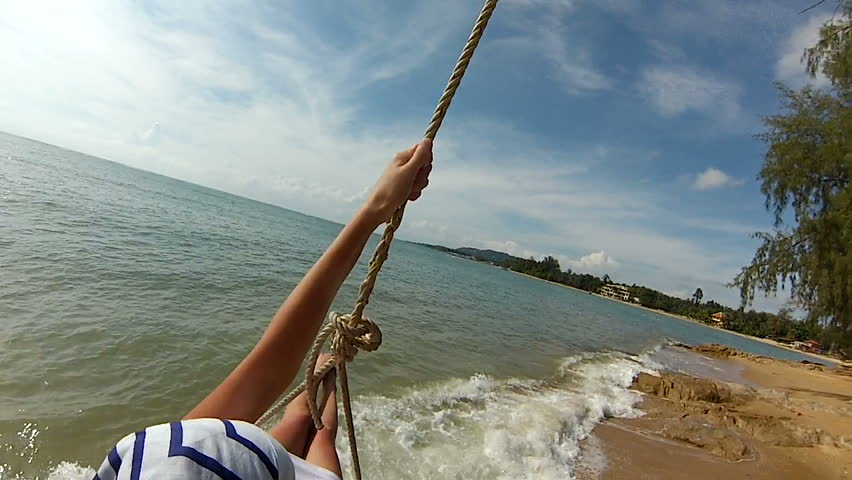 Young girl headscarf and white dress on a rope swing next to the sea the ocean gopro. | Shutterstock HD Video #22793755